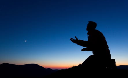 Man pleading on the summit of a mountain at sun set with the moon in the sky.